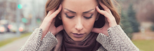 portrait photo of woman outdoors with hands to head or ears looking stressed