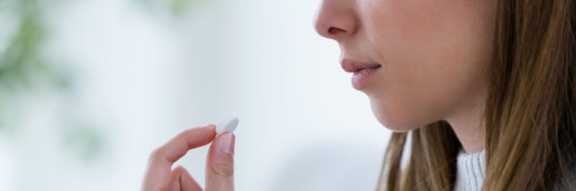 photo of young woman with a glass of water and white pill