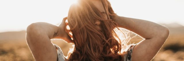 photo of woman with dark blonde hair with hands in hair silhouetted against sun