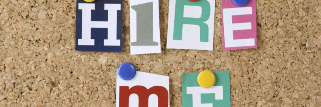 """Cutout letters that say """"Hire Me"""" on cork board."""