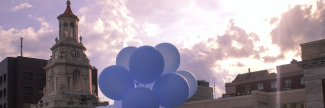 Blue balloons floating from a roof.