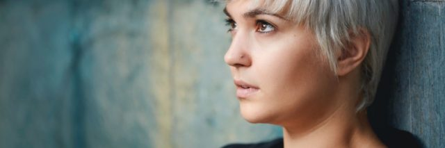 photo of woman with short light hair leaning against wall