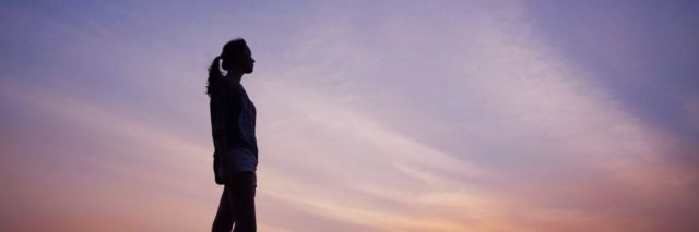 photo of woman standing alone silhouetted against sunset sky