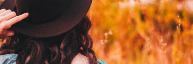 photo of woman wearing hat over long brown hair standing in front of orange grass or wheat