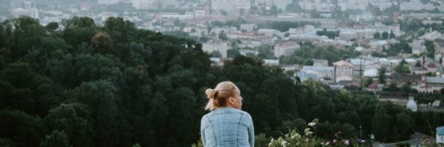 photo of young woman standing alone looking out over city