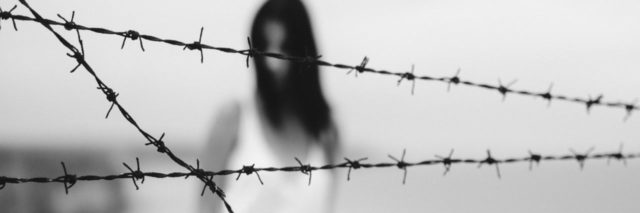 blurred black and white photo of silhouetted woman with crossed barbed wire in focus in foreground