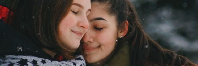 photo of two young women embracing in winter with smiles