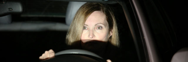 a woman is in a car behind the wheel with headlights shining in her face