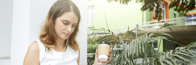young woman taking notes and drinking coffee with earbuds on