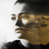 Double exposure of woman and orange cloudscape