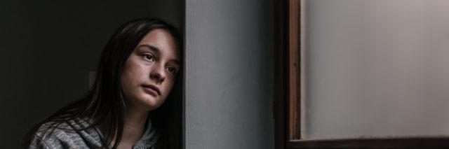woman looking contemplative near a window