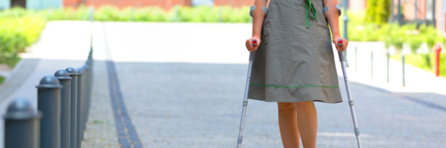 Woman walking with crutches outdoors.