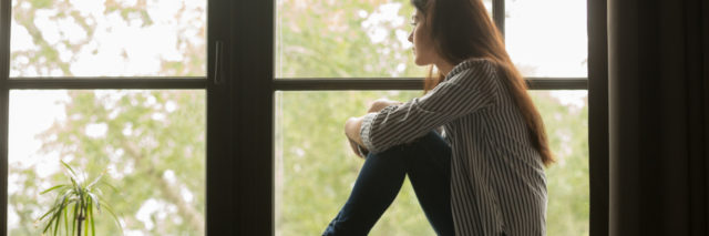 photo of woman sitting on windowsill looking out of window thoughtfully and hugging her knees