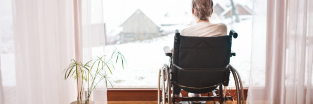 photo of woman from behind sitting in wheelchair looking out of window