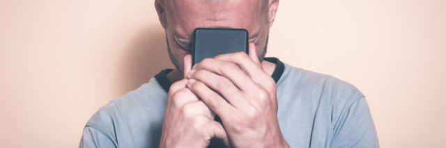 photo of man holding phone in hands and close to face, crying