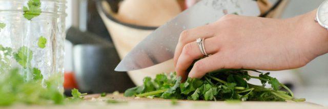 woman chopping herbs on a cutting board