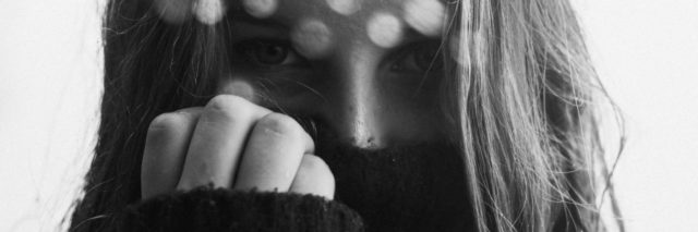 black and white close up photo of woman covering most of face with clothing and hand up to face, looking into camera with angry look