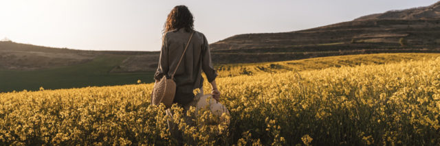 a woman alone walking in a field of flowers