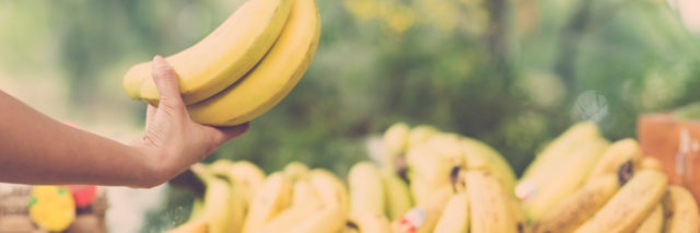 Image of a human hand holding a bunch of ripe bananas on the foreground