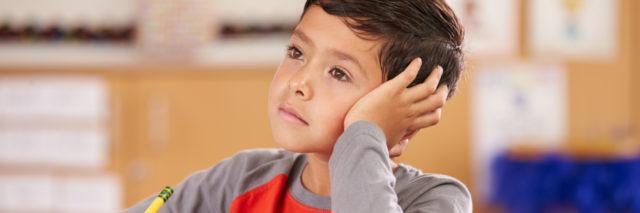 Boy daydreaming in an elementary school class.
