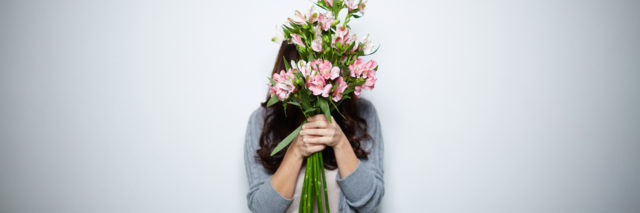 A woman hiding behind a bouquet of flowers
