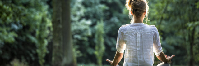 a woman meditating outdoors