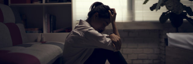 woman sitting on the floor in her living room. her head is in her hands and she appears upset. the blinds are drawn so the room is dark.