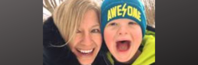 Mother and son with Down syndrome smiling at camera