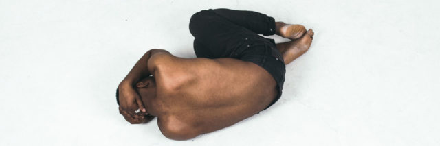 A black shirtless man laying in fetal position on the floor with his hands covering his head.