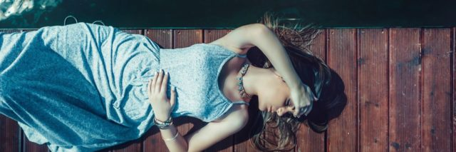 photo of woman lying on wooden dock covering eyes with arm