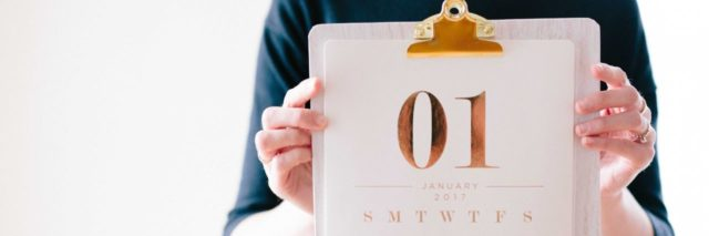 photo of woman holding up calendar showing first page in january