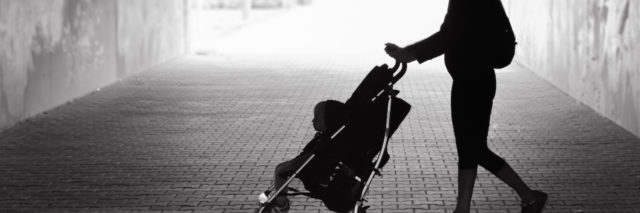 A woman walking her baby in a stroller