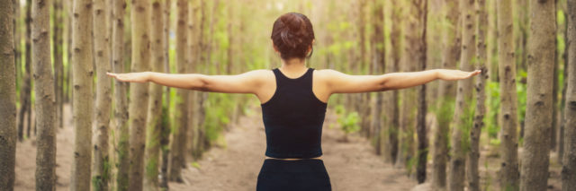 a woman is spreading her arms in the forest