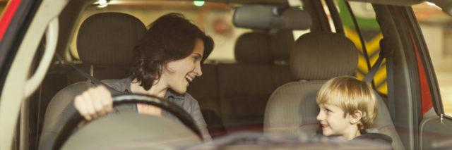 Woman talking to boy in car.