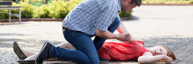 Man trying to help unconscious woman on the street.