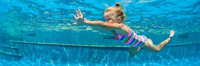 A young girl swimming in a pool, underwater shot