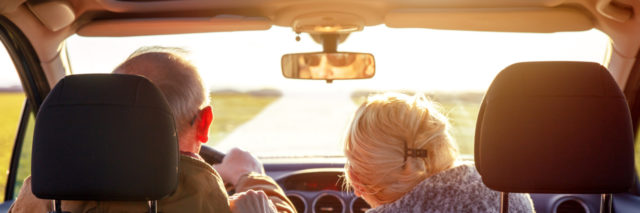 Rear view of smiling elderly couple driving car.