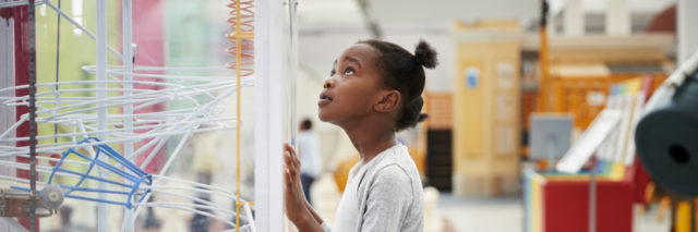 Young black girl looking at a science exhibit.