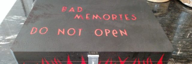 "photo of black painted box with silver lock and painted red flames. On the top is written ""bad memories, do not open"""