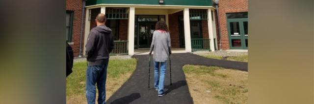 woman walking on asphalt path with her walker toward a brick building