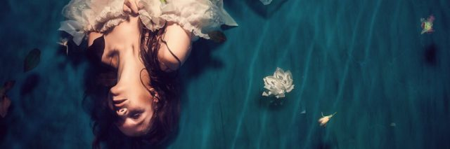 photo of woman in white dress lying in water looking up