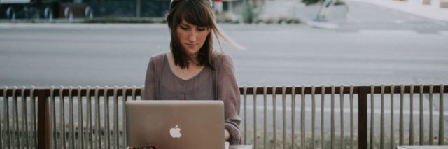 photo of woman writing on laptop outside coffee shop with road behind her