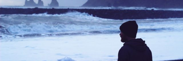 photo of man looking out to rough ocean and rocky coast