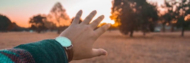 photo of woman's hand reaching out to sunset in area with trees