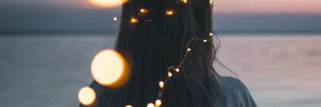 photo of woman looking out at lake with fairy lights leading from camera to her hair