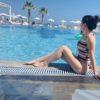 woman in bathing suit posing by a pool