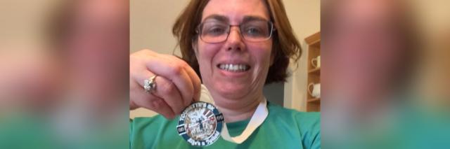Minda holding her 5K medal.