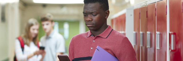 Portrait Of Male High School Student Bullied By Text Message In Corridor