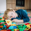 sad child, stress and depression, exhaustion with toys scattered around