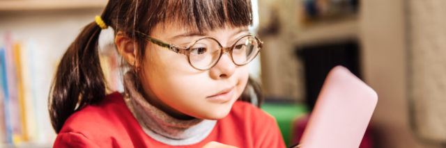 Girl with Down syndrome at school using a tablet with a stylus